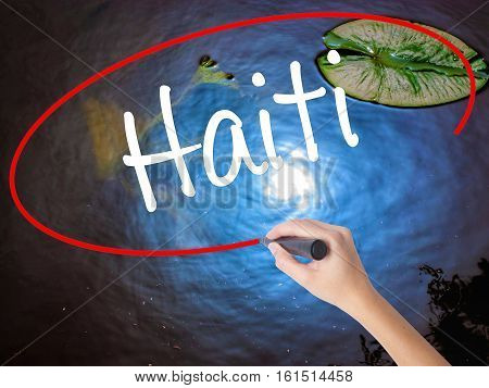 Woman Hand Writing Haiti With Marker Over Transparent Board