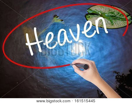 Woman Hand Writing Heaven With Marker Over Transparent Board