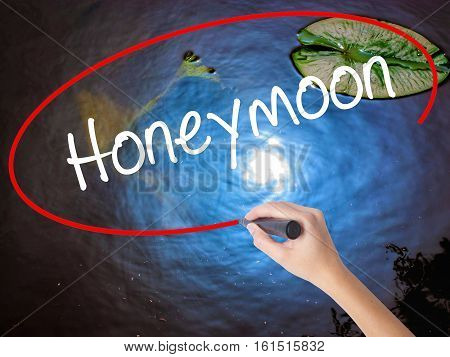 Woman Hand Writing  Honeymoon  With Marker Over Transparent Board
