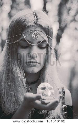 Young witch with a skull candle in her hands black and white photo soft focus faded colors