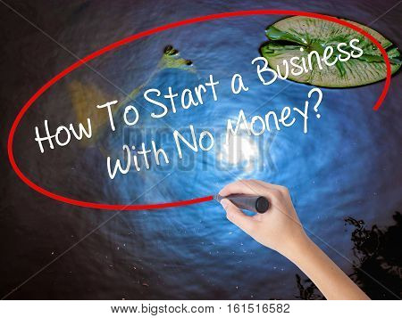 Woman Hand Writing How To Start A Business With No Money? With Marker Over Transparent Board