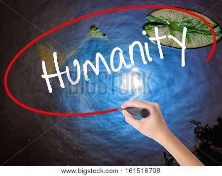 Woman Hand Writing Humanity  With Marker Over Transparent Board