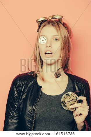 Pretty girl or young cute beautiful woman or watchmaker with red hair keeps cogwheel on eye and mechanical metallic gears on orange background
