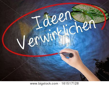 Woman Hand Writing Ideen Verwirklichen ( Realize Ideas In German) With Marker Over Transparent Board