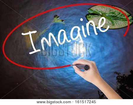 Woman Hand Writing Imagine  With Marker Over Transparent Board