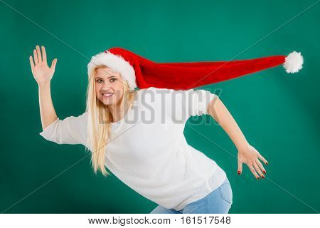 Christmas accessories fun and joy concept. Woman wearing windblown long Santa hat fooling around running somewhere. Studio shot on green background