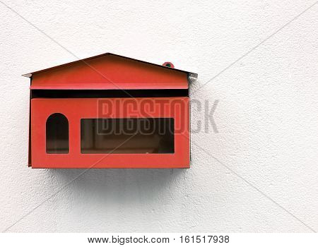 empty red mailbox on white concrete wall, metal mailbox shaped like a home