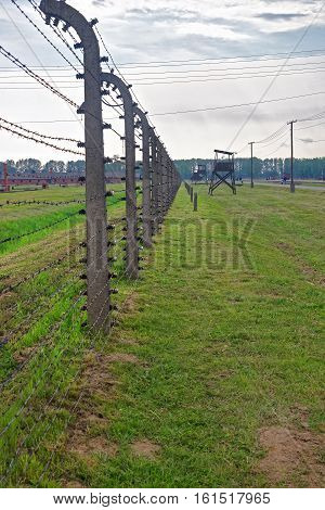 Oswiecim, Poland - May 2, 2014: Barbed wire and Watch tower at concentration camp Auschwitz Birkenau Poland.