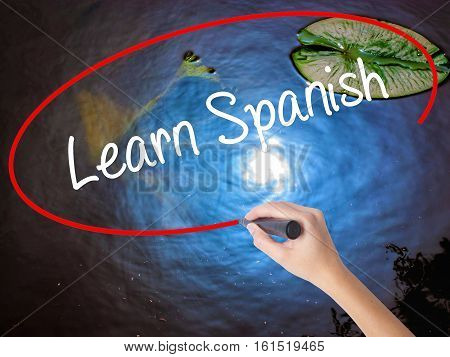 Woman Hand Writing Learn Spanish With Marker Over Transparent Board