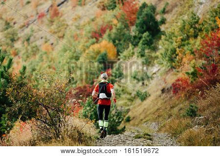 male athlete competes in skyrunning steep descent in autumn forest