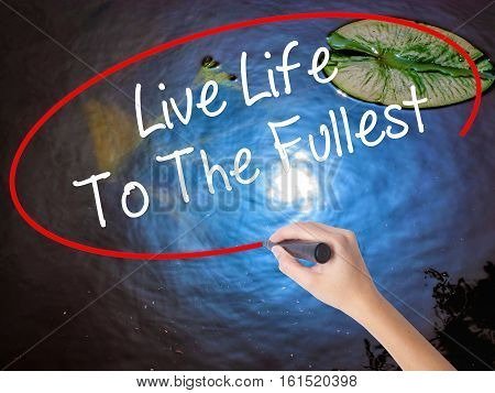 Woman Hand Writing Live Life To The Fullest With Marker Over Transparent Board