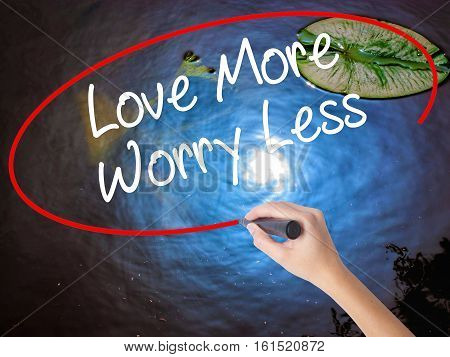 Woman Hand Writing Love More Worry Less With Marker Over Transparent Board.