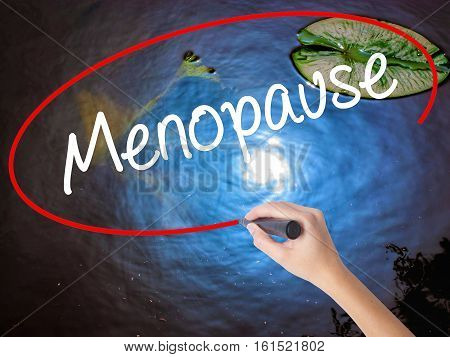 Woman Hand Writing Menopause With Marker Over Transparent Board.