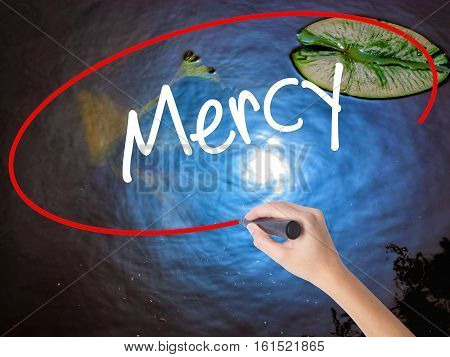 Woman Hand Writing Mercy With Marker Over Transparent Board