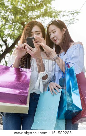 Happy Asian Woman With Smartphone And Colorful Shopping Bags At Park