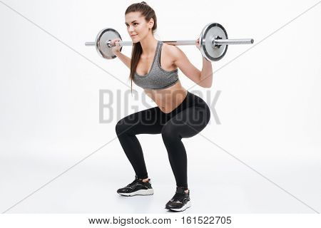 Portrait of a focused smiling fitness woman doing squats with barbell isolated on a white background