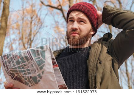 Portrait of confused bearded man wearing hat holding map in hands standing in the forest. Look aside.