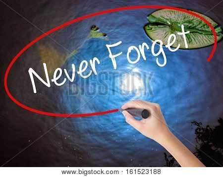 Woman Hand Writing Never Forget  With Marker Over Transparent Board