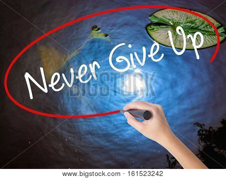 Woman Hand Writing Never Give Up With Marker Over Transparent Board