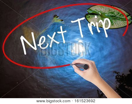 Woman Hand Writing Next Trip With Marker Over Transparent Board