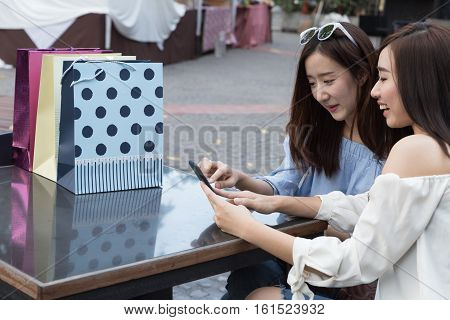 Happy Asian Woman With Smartphone And Colorful Shopping Bags At Cafe Restaurant