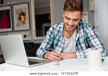 Picture of cheerful bristle man dressed in shirt in a cage print sitting in home and using laptop computer while writing notes for analyzing home finances.