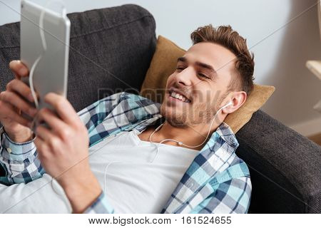 Image of cheerful bristle man dressed in shirt in a cage print lies on sofa in home and using tablet computer while listening music with earphones. Looking at tablet computer.