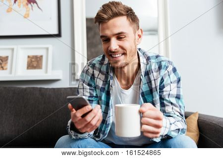 Image of cheerful young bristle man dressed in shirt in a cage print sitting on sofa in home and holding cup of tea while chatting.
