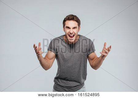 Portrait of an excited young man with both hands up isolated on the gray background