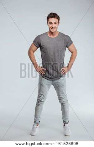 Full length portrait of a handsome man standing with hands on hips over white background and looking at camera
