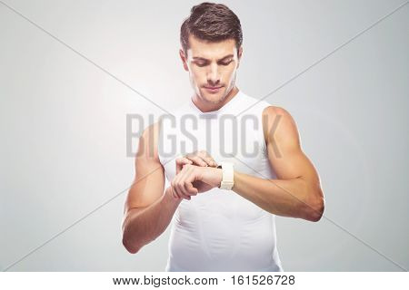 Handsome fitness man using smart watch over gray background