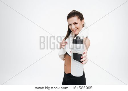 Portrait of a happy smiling sports woman passing a water bottle to camera with towel around her neck isolated on a white background
