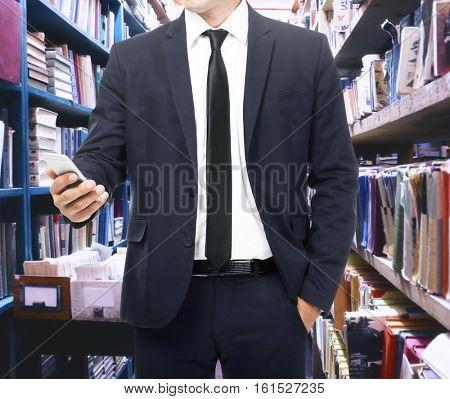Man with phone at library, closeup. Law and justice concept.