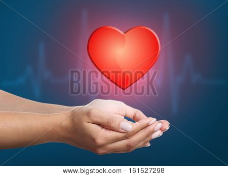 Female hands with heart on dark background. Cardiology concept.