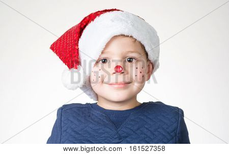 lovely and adorable child boy with Christmas face paint an hat