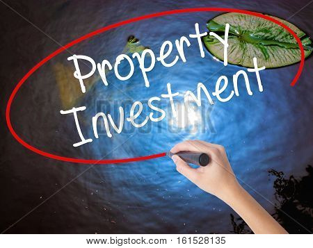 Woman Hand Writing Property Investment With Marker Over Transparent Board