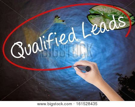 Woman Hand Writing Qualified Leads With Marker Over Transparent Board
