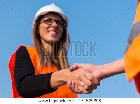 Civil Engineers Handshaking On Construction Site