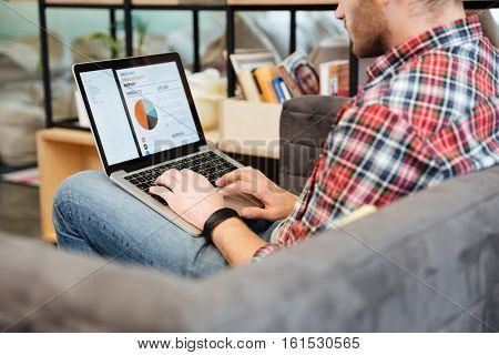 Back view of man analyzes performance on laptop and sitting on sofa in office. Side view, Coworking