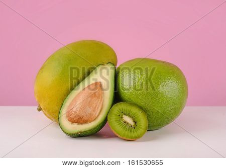 Green pomelo fruit, sliced avocado and kiwi on a table isolated on pink background