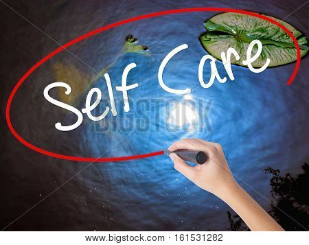 Woman Hand Writing Self Care With Marker Over Transparent Board