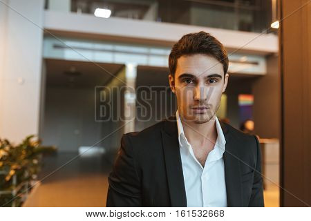 Serious business man in suit looking at camera in office