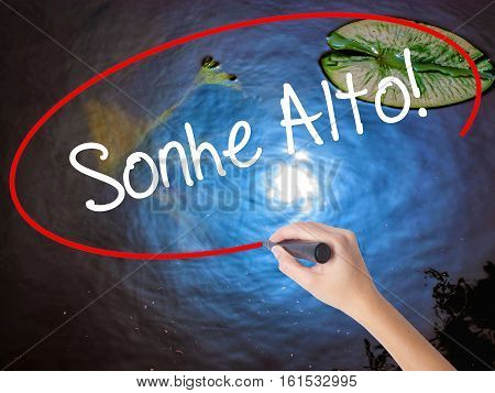 Woman Hand Writing Sonhe Alto! (dream Big In Portuguese) With Marker Over Transparent Board
