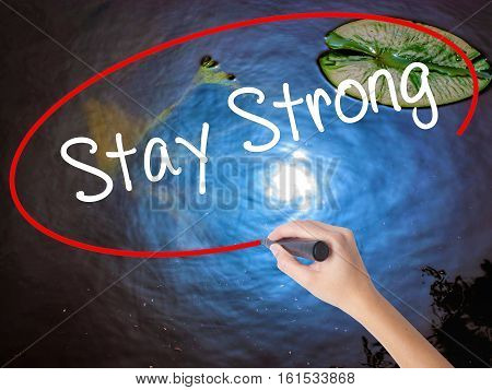 Woman Hand Writing Stay Strong With Marker Over Transparent Board.
