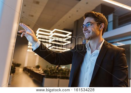 Smiling Business man in suit and glasses standing in office and pointing on something