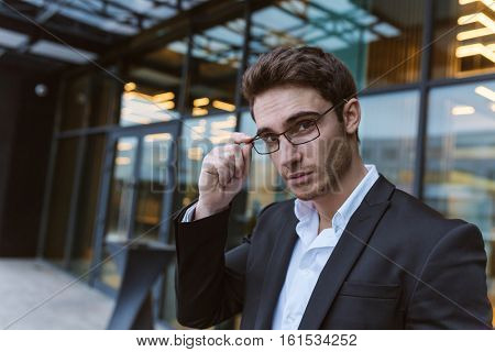 Business man in suit and glasses standing near the office and looking at camera
