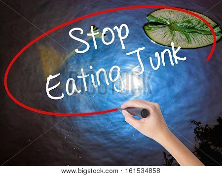 Woman Hand Writing Stop Eating Junk With Marker Over Transparent Board.
