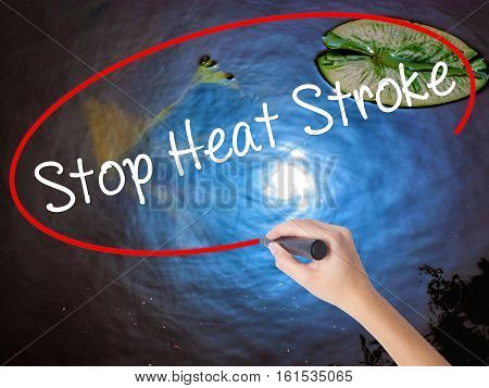 Woman Hand Writing Stop Heat Stroke With Marker Over Transparent Board.