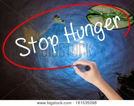 Woman Hand Writing  Stop Hunger With Marker Over Transparent Board