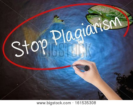 Woman Hand Writing Stop Plagiarism With Marker Over Transparent Board